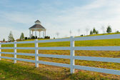 Gazebo in the new city park behind white fence — Stock Photo