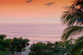 Sunset at tropical resort with view of ocean — Stock Photo