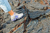 Foot on the stones of volcanic flow — Stock Photo