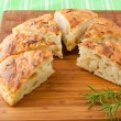 Homemade round Italian rosemary Focaccia bread sliced. — Stock Photo