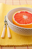 Half of ruby red grapefruit in a bowl ready to eat. — Stock Photo