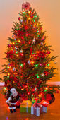 Decorated Christmas tree surrounded by gifts wrapped presents an — ストック写真