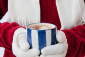 Woman in warm gloves holding cup of hot chocolate with marshmall — Stock Photo