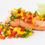 Salmon fillet with mango salsa on white plate. — Stock Photo
