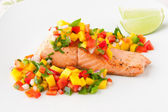 Salmon fillet with mango salsa on white plate. — Stockfoto