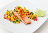Salmon fillet with mango salsa on white plate. — Stock Photo