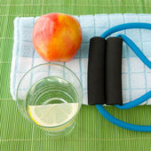 Healthy lifestyle concept - water, apple, expander and towel. — Stockfoto