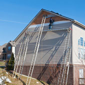 Workers installing plastic siding panels on two story house. — Foto de Stock