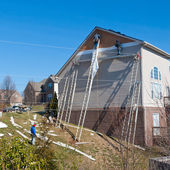 Workers installing plastic siding panels on two story house. — Stock Photo