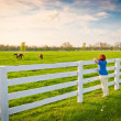 Woman  enjoying  countryside  view  with green pastures and hors - Photo
