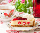 Piece of strawberry cheesecake with edible letters for Valentine — Stock Photo