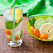 Cold fresh drink with lemon, lime, kumquat and mint. — Stock Photo