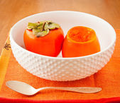 Persimmons in bowl with spoon — Stock Photo