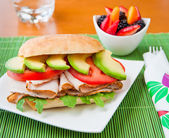 Sandwich with turkey, tomato, avocado and arugula. — Foto de Stock