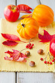 Apples, leaves and golden acorn squash on wood table — Stock Photo