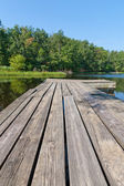 Small country lake with wooden pier. — Stock Photo