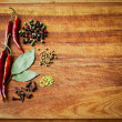 Dried red chili peppers and spiceson rustic, dark wood cutting board. — Stock Photo