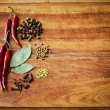 Dried red chili peppers and spiceson rustic, dark wood cutting board. — Stock Photo #30970361
