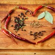 Dried red chili peppers and spices in heart shape on rustic, dark wood cutting board. — Stock Photo