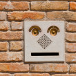 A modern intercom doorbell  panel on old brick wall. — Foto de Stock