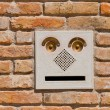 A modern intercom doorbell  panel on old brick wall. — Photo