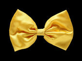 Gold satin gift bow. Ribbon. Isolated on black with clipping pat — Stock Photo