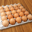 Carton of fresh brown eggs on Wood background — Stock Photo