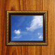 A photo of a wooden picture frame with the sky setting inside — Stock Photo