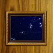 A photo of a wooden picture frame with the night sky setting ins - Stock Photo