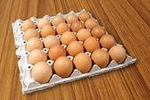 Carton de œufs frais de bruns sur fond de bois — Photo