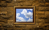 A photo of a wood frame on brick wall with the sky setting inside — Stock Photo