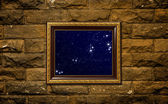 A photo of a wood frame on brick wall with the night sky setting inside — Stock Photo