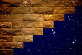 Night sky with light through the hole in the brick wall — Stock Photo
