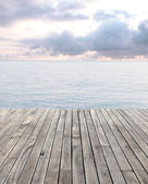 Wooden floor and blue sea with waves and cloudy sky — Stock Photo