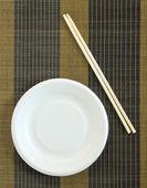 Beyaz tabak ve yemek çubukları — Stok fotoğraf
