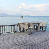 Wooden table and chairs on a tropical beach resort — Stock Photo