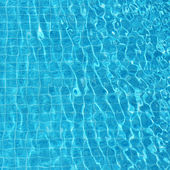 Blue rippled water background in swimming pool — Stock Photo