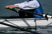 Woman rowing on a white rower — Stock Photo