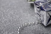 Silver gift box on gray brilliant background — Stock Photo