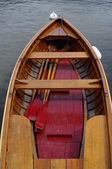 Wooden small boat and red paddles — Stock Photo