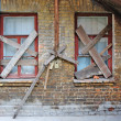 Stock Photo: Old abandoned house brick wall with covered windows