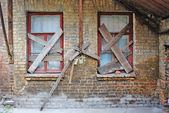 Old abandoned house brick wall with covered windows — Stock Photo