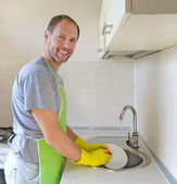 Smiling man washing dish in the kitchen — Stock Photo