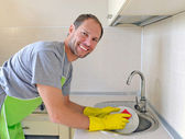 Smiling man washing dish in the kitchen — Stok fotoğraf