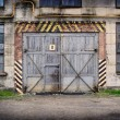 Stock Photo: Abandoned old factory with closed door and windows