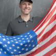 Smiling man in gray against background of the USA flag — Stock Photo