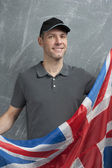 Smiling man in gray against background of the British flag — Stock Photo