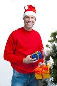 Smiling christmas man wearing a santa hat at the Christmas tree — Stock Photo
