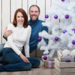 Smiling couple near a Christmas tree — Stock Photo