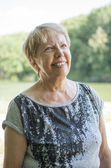 Smiling senior woman walking in the park — Stockfoto